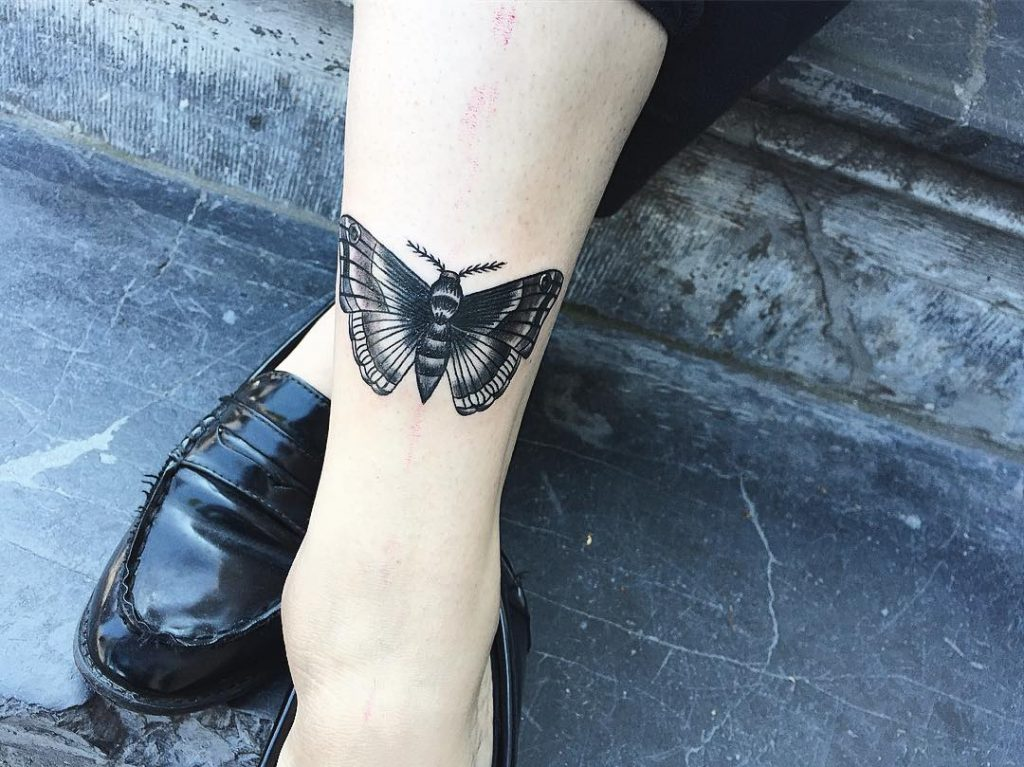 Lovely black moth shin tattoo