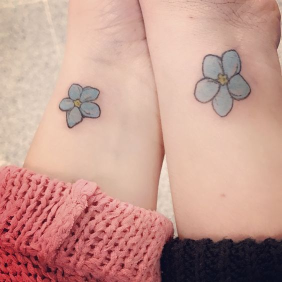 Matching forget me not tattoos on wrists