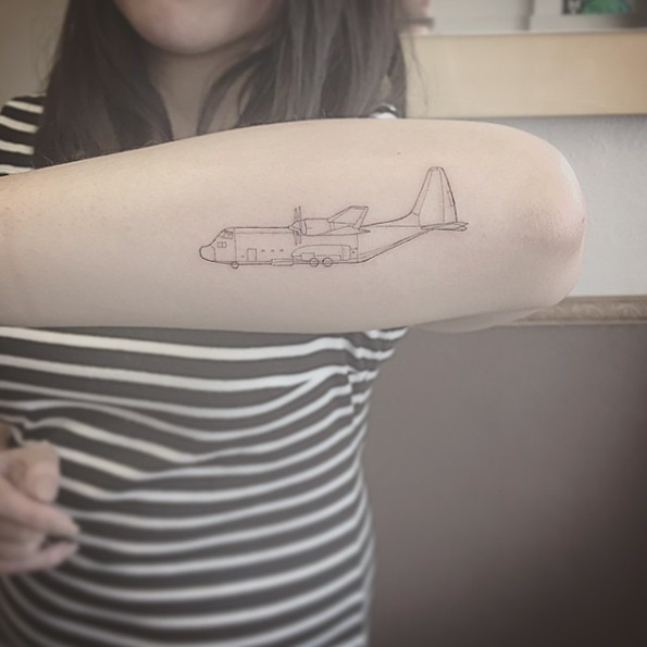 Military transport aircraft tattoo on the forearm