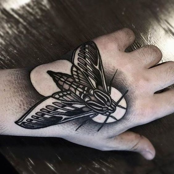 Monochrome black and grey moth tattoo on the left hand