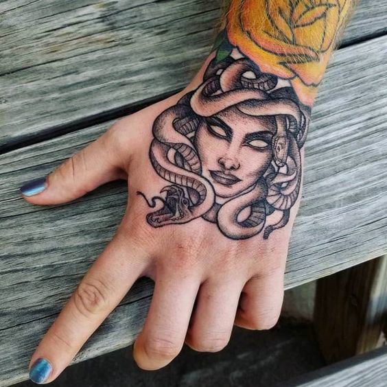 Monocrhome black medusa tattoo on the hand