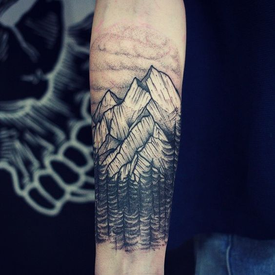 Mountains and forest tattoo on the forearm