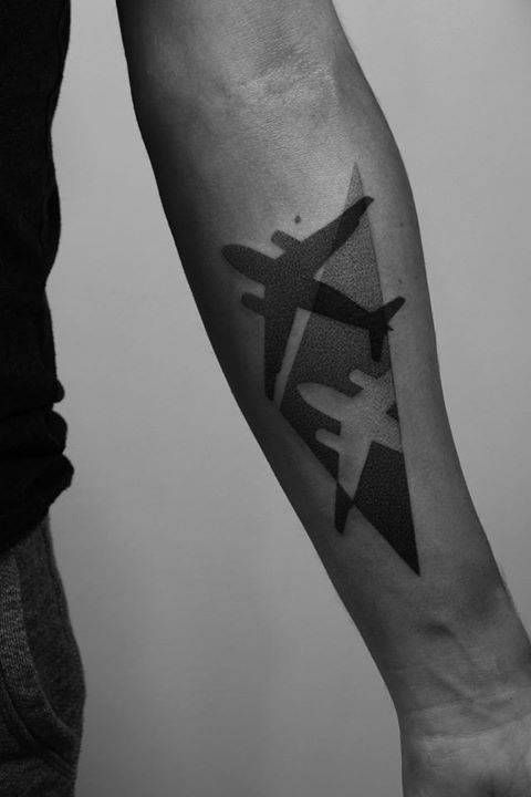 Negative space dotwork style airplane on the left forearm
