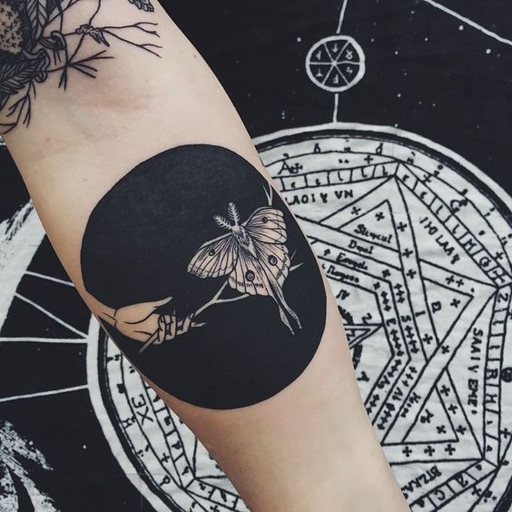 Negative space moth and hand tattoo on the arm