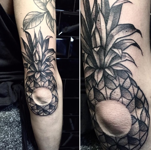 Negative space pineapple tattoo around the elbow