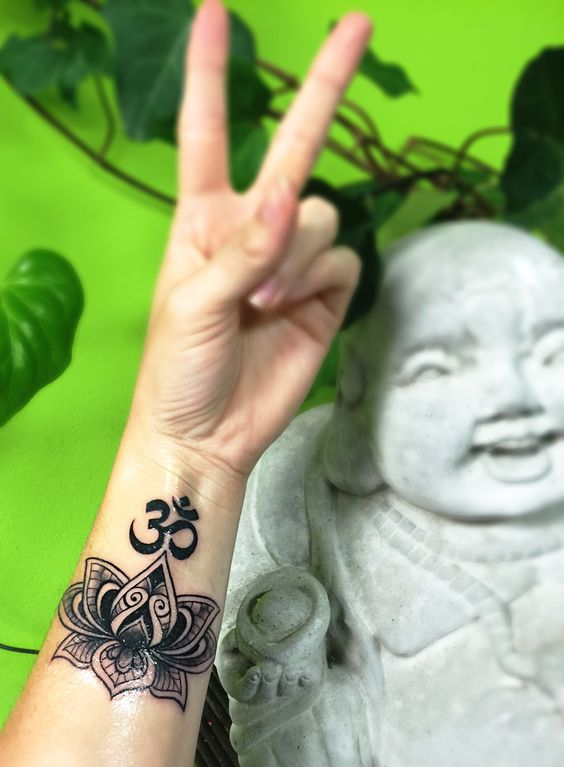 Om and lotus flower on the wrist