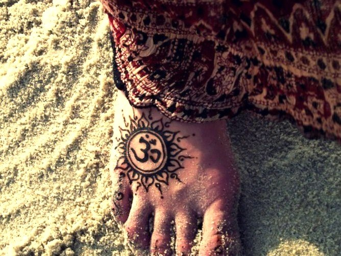 Om and sun tattoo on the foot