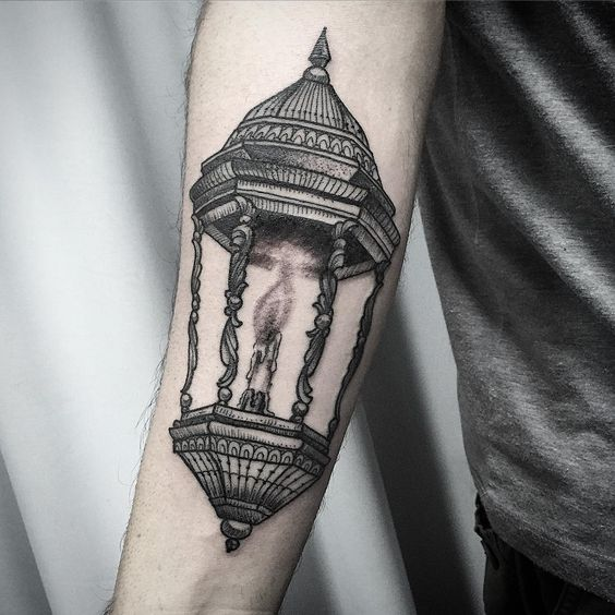 Ornamental lantern with a burning candle tattoo on the forearm