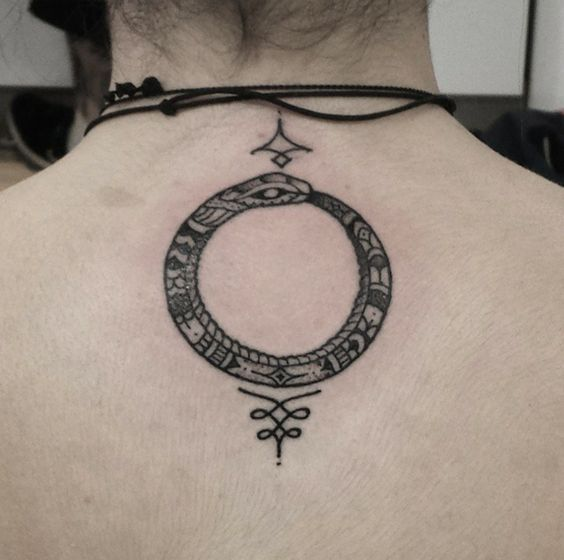 Ornamental ouroboros back tattoo