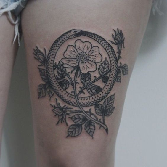 Ouroboros among the flowers tattoo