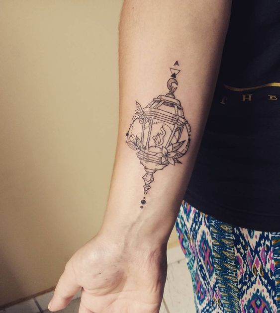 Outline small tattoo of a lantern on the right forearm