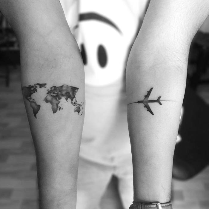 Plane and world map tattoos on both forearms