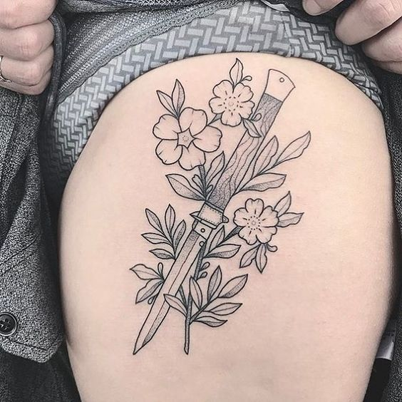 Pocket knife and flowers outline tattoo on the left thigh