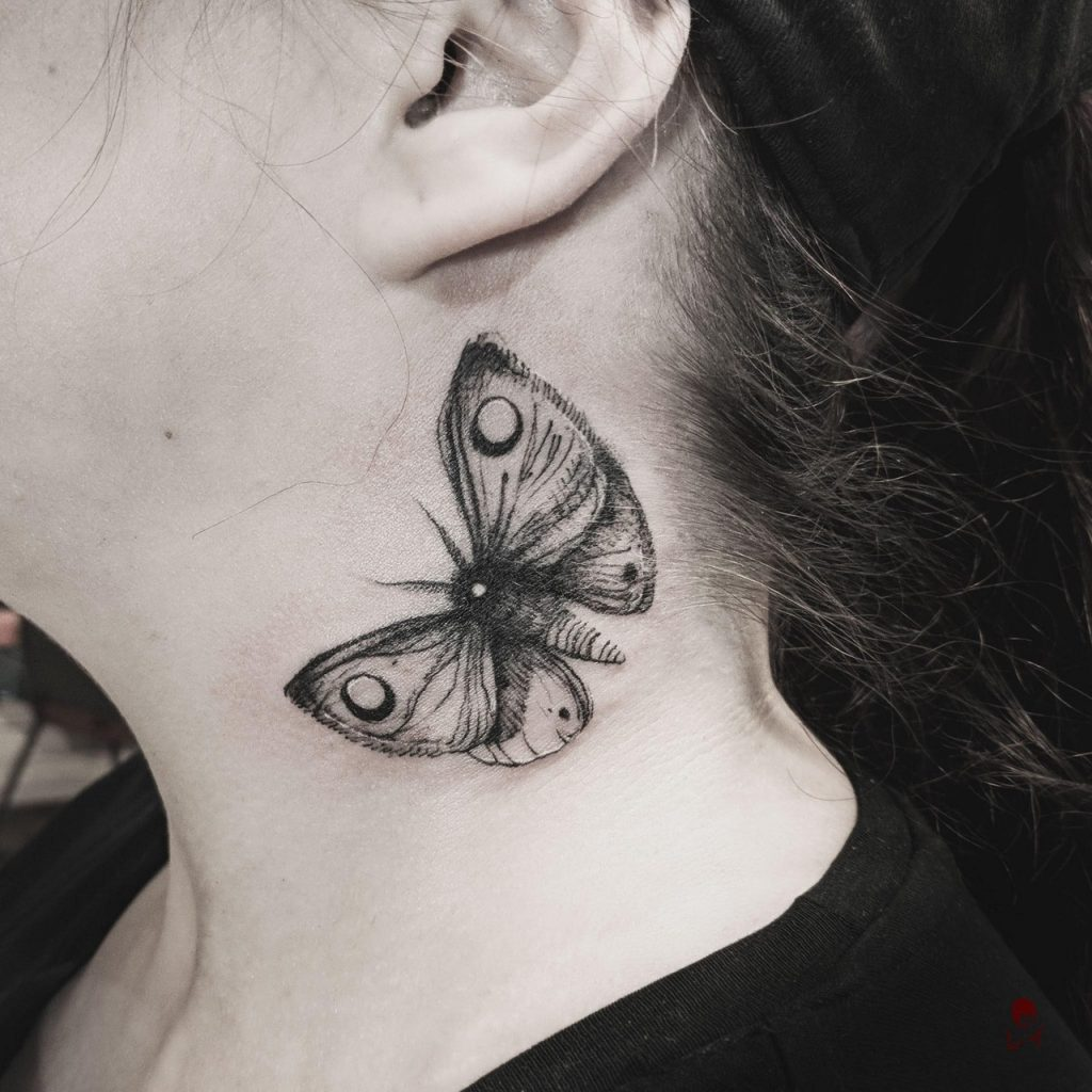 Realistic black moth on the left side of the neck