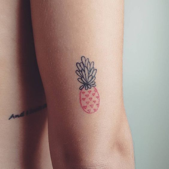 Red small pineapple tattoo on the back of the arm