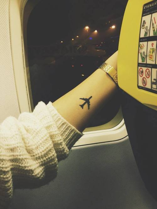 Solid black airplane tattoo on the left forearm
