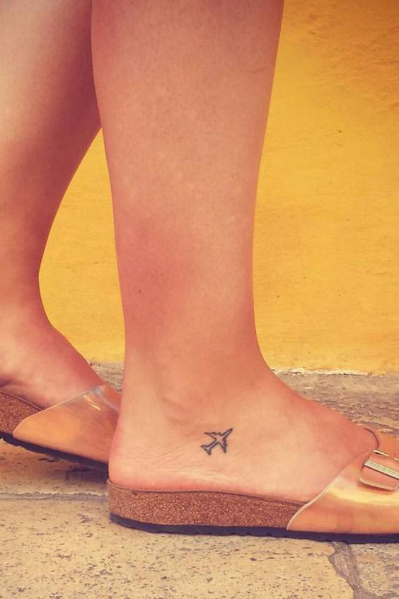 Super tiny outline airplane tattoo on the right foot
