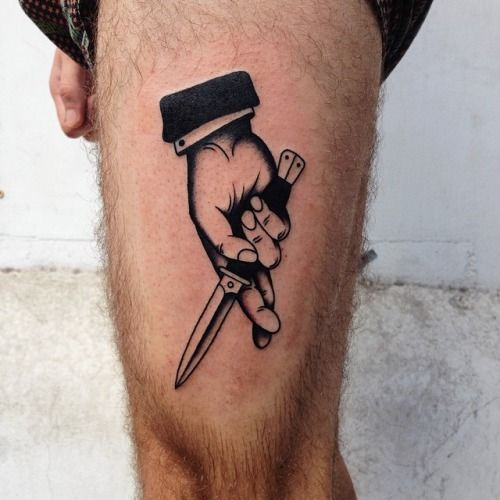 Switchblade in a hand tattoo on the left thigh