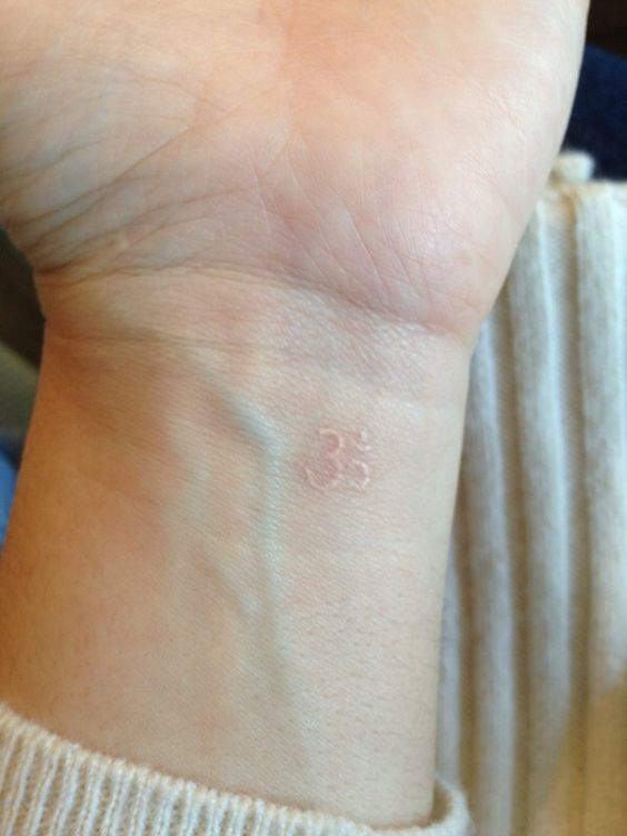 Tiny white om on the inner wrist
