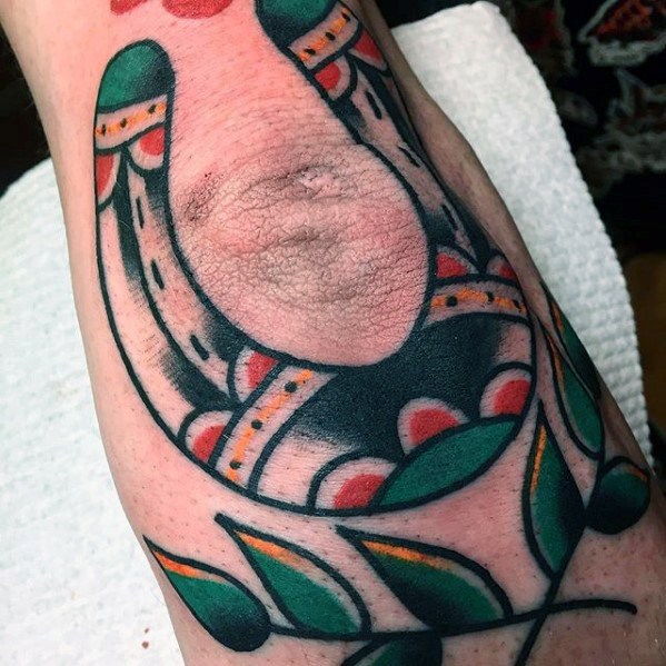 Traditional horseshoe and branches tattoo on the elbow