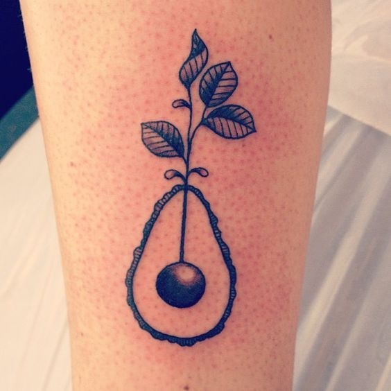 Black and grey avocado tattoo with the leaves on top