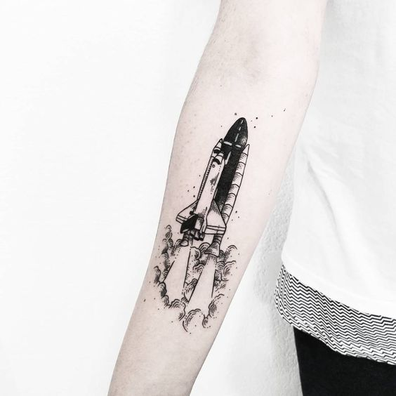 Black spaceplane tattoo on the right inner forearm