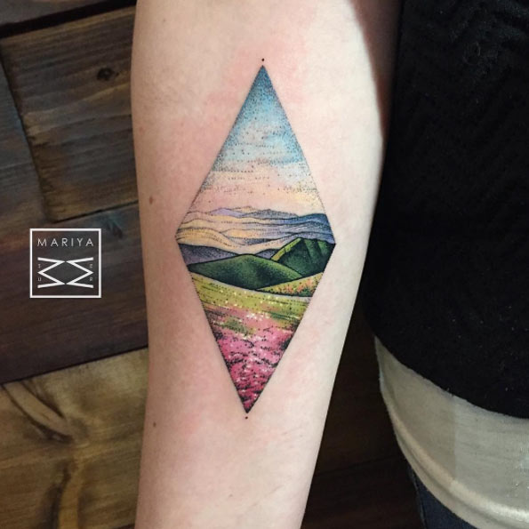 Colorful valley landscape tattoo on the inner forearm