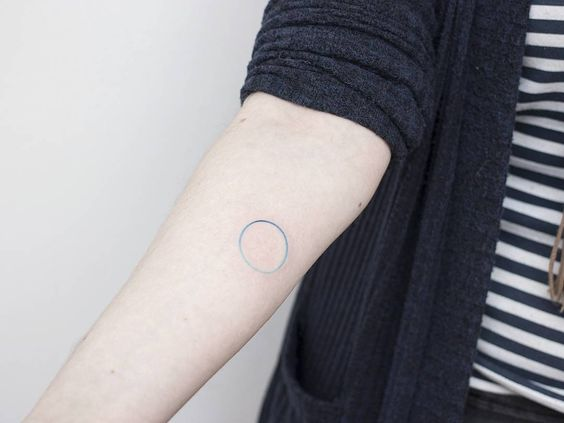 Gradient blue circle tattoo on the forearm