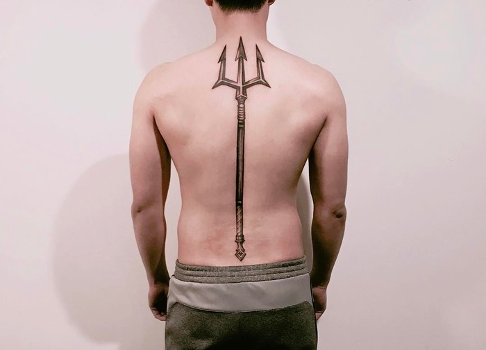 Large trident tattoo on the back