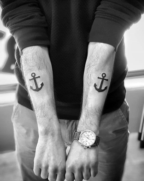 Matching anchor tattoos on both forearms