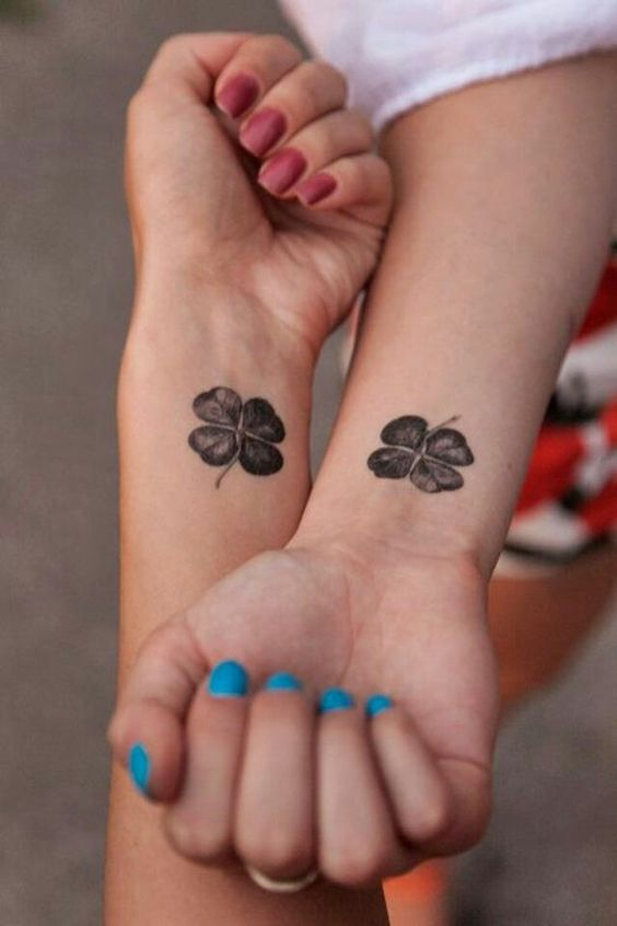 Matching black clover tattoos on wrists