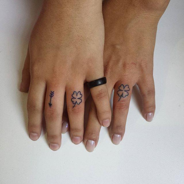 Matching clover tattoos on the fingers