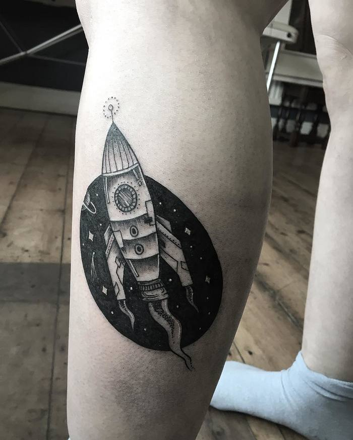 Negative space spaceship tattoo on the calf
