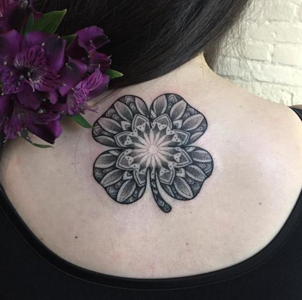 Ornamental black four leaf clover tattoo on the back