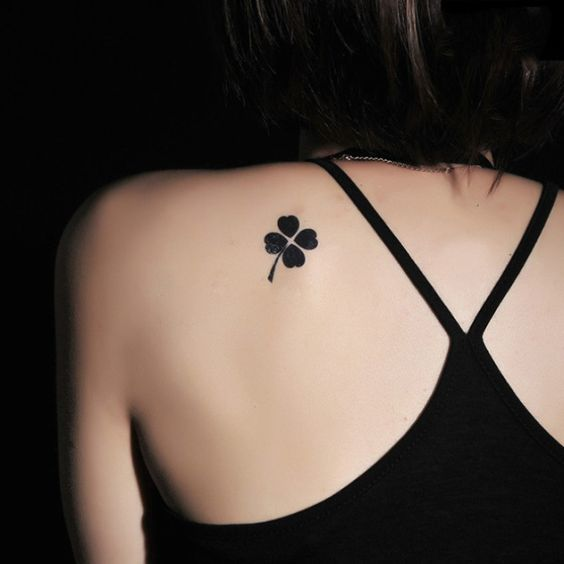 Pure black four leaf clover on the left shoulder blade