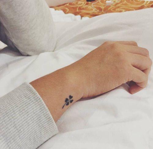 Small black four leaf clover on the wrist
