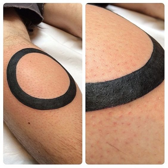 Solid black circle tattoo on the left calf