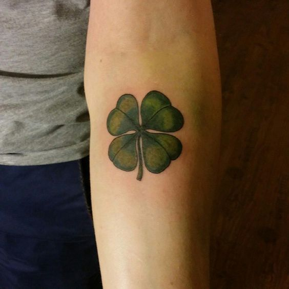 Subtle green clover tattoo on the inner arm