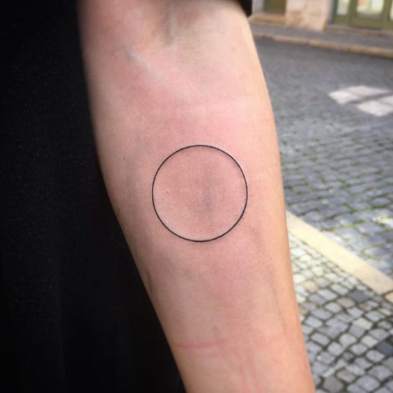 Thin black circle tattoo on the left inner forearm