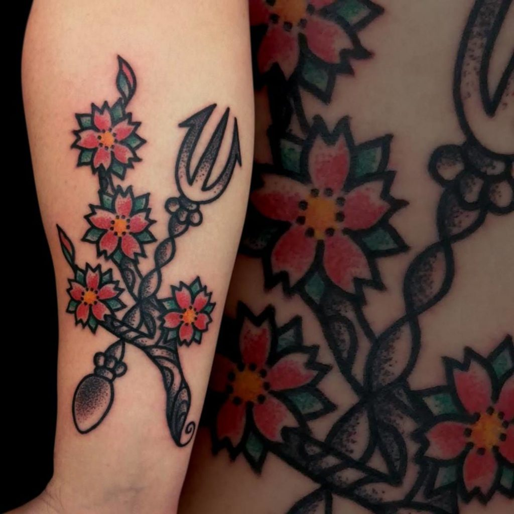 Traditional style little tattoo of a trident and flowers