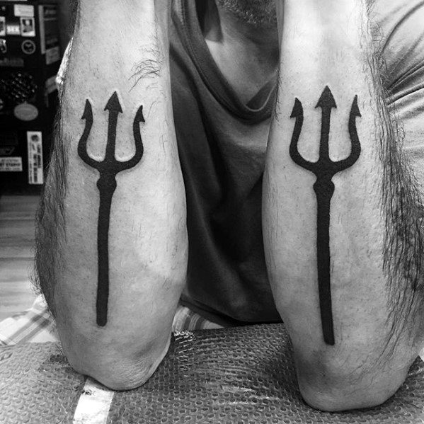 Two matching trident tattoos on the forearms