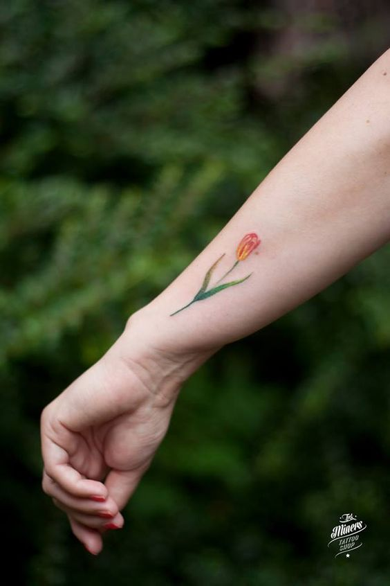 A small orange tulip tattoo by magdalena bujak