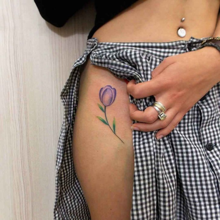 Purple tulip tattoo on the right hip