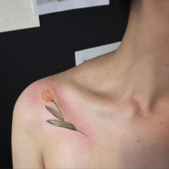 Yellow tulip tattoo on the collarbone