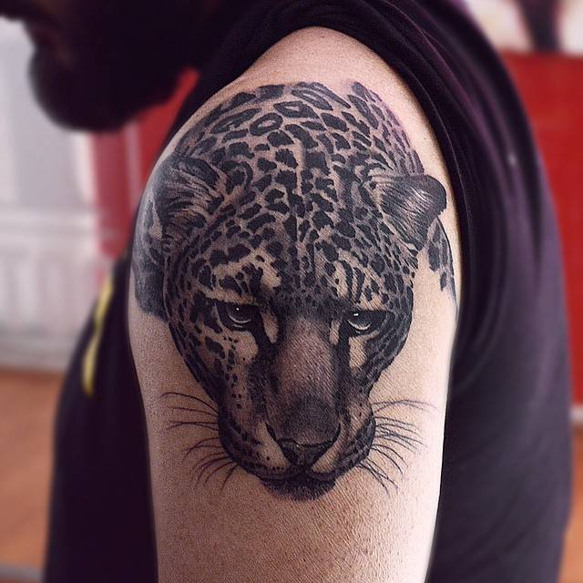Black and grey leopard tattoo on the right shoulder