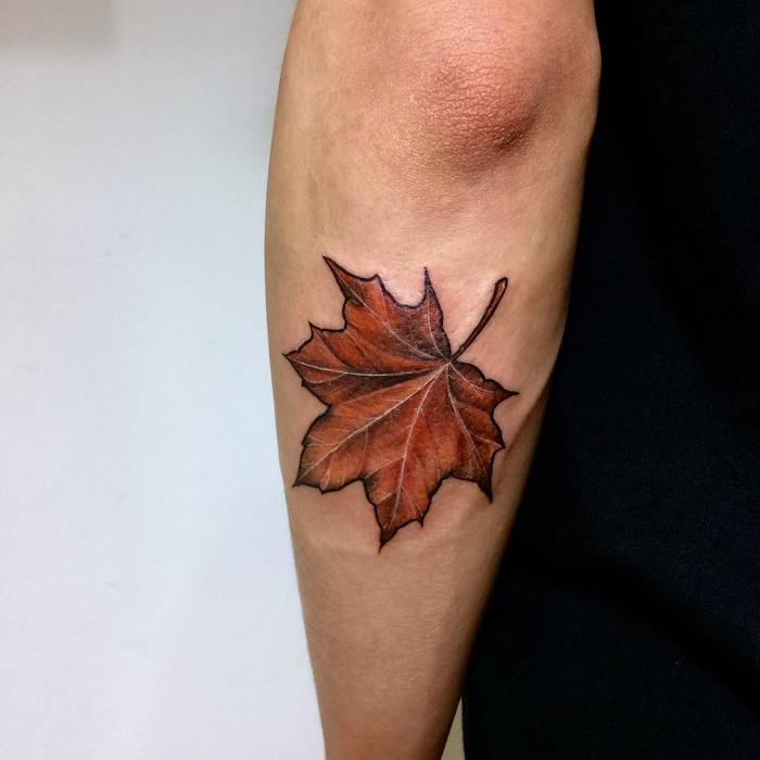 Brownish maple leaf on the back of the left forearm