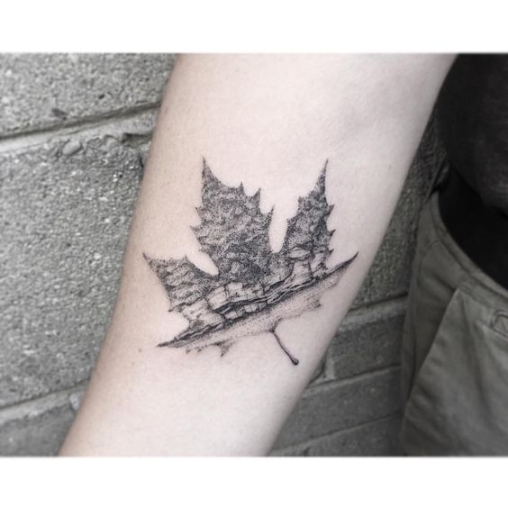Dot work style maple leaf with a landscape on it
