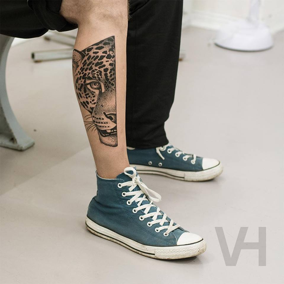 Leopard's head tattoo on the shin