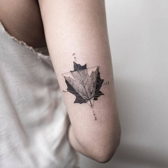 Maple leaf and compass tattoo