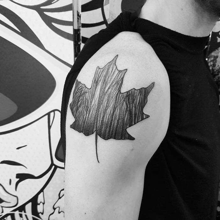Maple leaf tattoo with a forest scenery